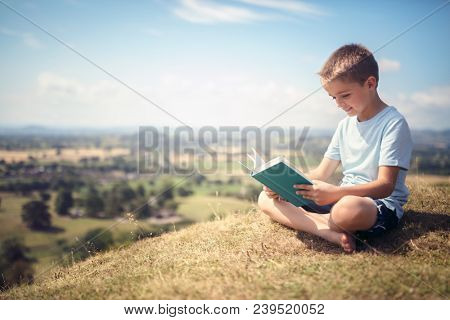 Boy sitting and relaxing on a hill reading a book in a meadow concept for education and relaxing