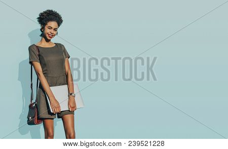 Beautiful Flirtatious African-american Undergraduate Girl Is Standing In Front Of The Wall Filled Wi