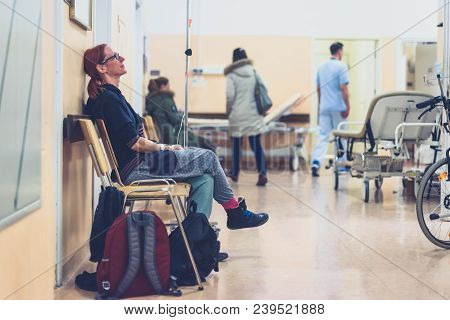 Patient Sitting In Hospital Ward Hallway Waiting Room With Iv