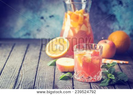 Refreshing Summer Drink Sangria Or Punch With Fruits In A Glass And Pincher Over Wooden Background
