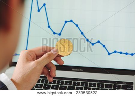 Man Holding Bitcoin And Background With Smart Phones, Laptops And Business Graphs - Concepts For Sta