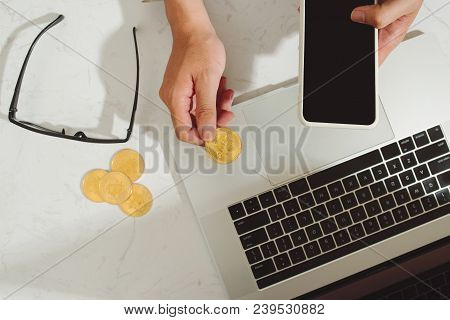 Hand Holding Mobilephone With Bitcoins With A Laptop Background Of Business Functions - Business And