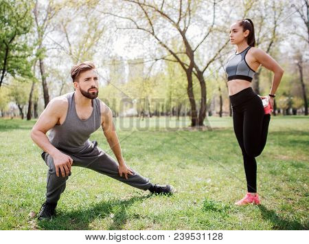 Beautiful Couple Is Stretching Outside In Park. Guy Is Squating And Stretching His Legs While His Gi
