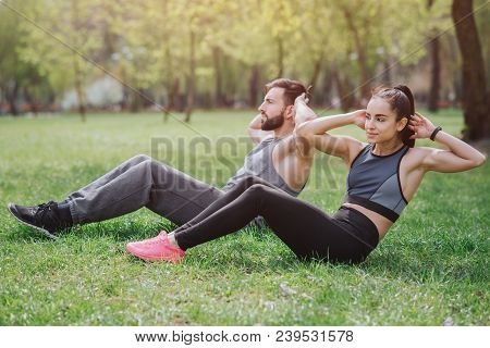Strong And Powerful People Are Working Out Outside In Park. They Are Doing Abs Exercises. Young Man