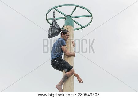 Tiraspol, Moldova - February 18, 2018: Young Man Climbing On A Wooden Pole For The Prize. Slavonic F