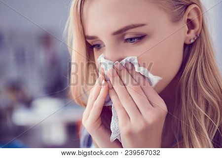 Concept Of Treatment For Allergies Or The Common Cold. Girl Blows Her Nose Into A Tissue.