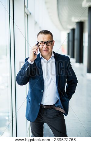 Businessman On The Phone. Confident Senior Man In Formalwear Talking On The Mobile Phone.