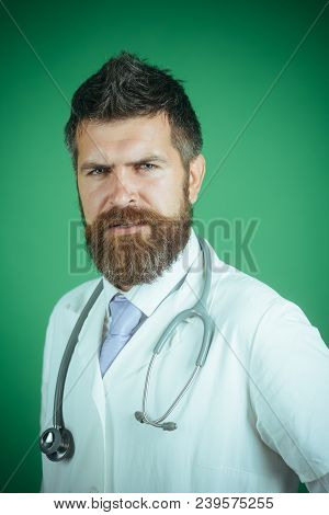 Physician With Beard Dressed In White Medical Robe. Medicine And Health Concept. Handsome Serious Do