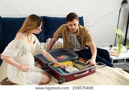 Pregnant Woman And Husband Packing Travel Bag For Vacation