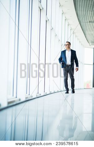 Full Length Picture Of A Mid Aged Business Man Walking Towards The Camera And Smiling In Office Buil