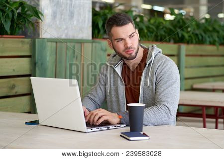 Pensive Freelancer In Sportswear Working On A New Project In The Cafe. A Serious Businessman With A