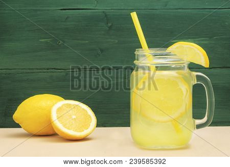 Mason Jar Glass Of Lemon Lemonade With Lemons And Straw On Table And Wooden Background. Cold Summer