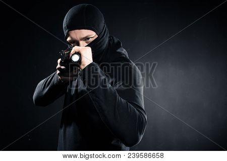 Burglar In Balaclava Aiming With Gun And Flashlight