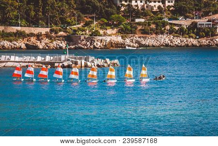 Nice, France - October 13, 2009: Group Of Yachtsmen With Red And White Sails Moving Along Coastline