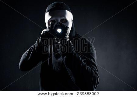 Burglar In Mask And Balaclava Aiming With Gun And Flashlight