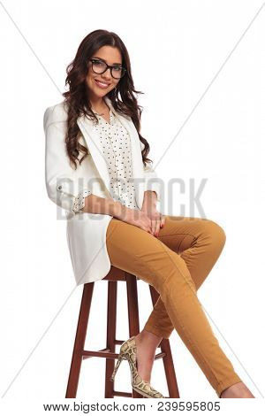 attractive businesswoman with eyeglasses sitting on chair with hands on thighs, on white background