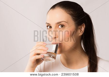The Woman Is Drinking Water From Drinking Glass For Hydration On White Background.