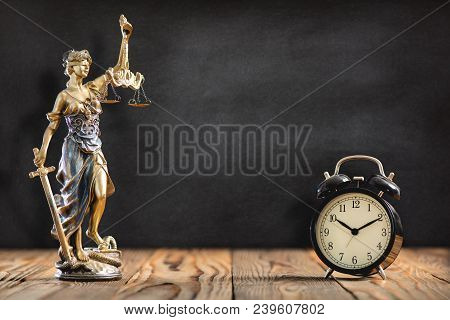 Statue Of Lady Justice With Alarm Clock On Black Board Background