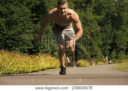 Man Run From Start Position On Road. Health And Active Lifestyle. Sportsman Runner With Muscular Tor