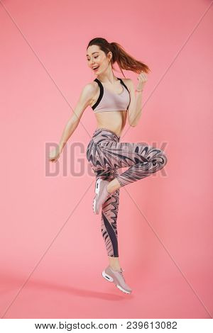Full length image of Happy sportswoman doing fitness exercise sideways and looking away over pink background