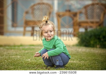 Small Child Sitting On Meadow Grass. Fun And Leisure Time. Nature And Environment. Childhood And Bab