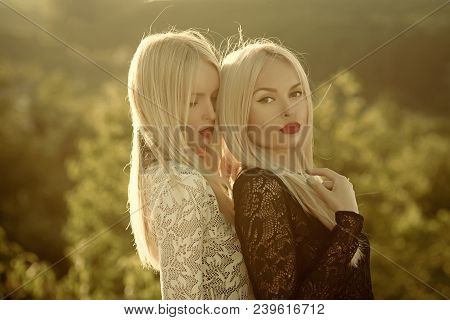 Sisters Twins Posing On Sunny Natural Landscape. Two Women With Red Lips And Long Blond Hair. Contra