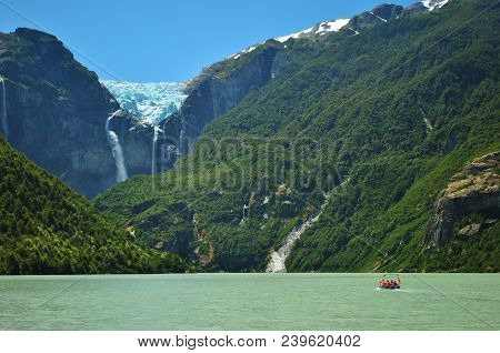 Small Orange Boat Full With Tourists In A Glacier Lagoon Or Lake With Green Water, With View Of A Ha