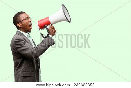 African black man wearing jacket communicates shouting loud holding a megaphone, expressing success and positive concept, idea for marketing or sales