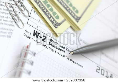 The Pen, Notebook And Dollar Bills Is Lies On The Tax Form W-2 Wage And Tax Statement. The Time To P