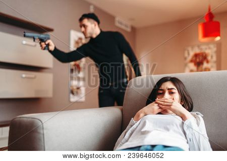 Woman hiding against killer with gun