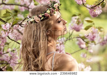 Delicate Blonde Girl In Blooming Garden.