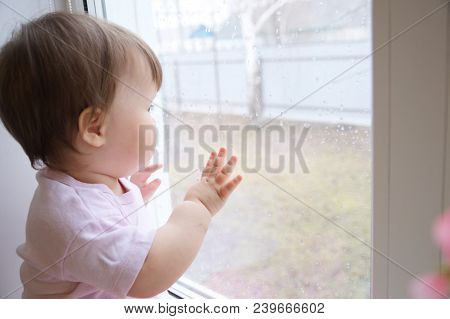 Child Looking Out The Window Longing For Some Sunshine  Because Of Rain. Curiosity Childness. Curiou