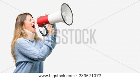 Young injured woman wearing neck brace collar communicates shouting loud holding a megaphone, expressing success and positive concept, idea for marketing or sales