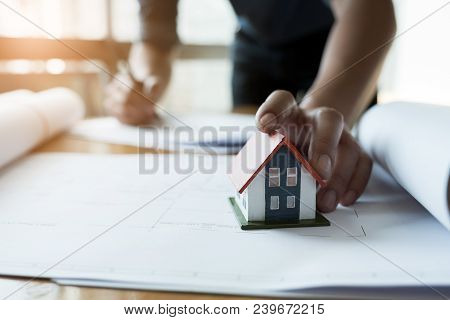 Close Up Hands Holding House Model, Engineer Working On Blueprint Construction Concept. Engineering