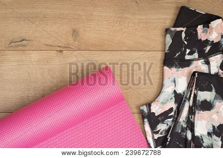 Pink Yoga Mat And Leggings In Flat Lay Style On A Wooden Background. Top View. Fashion Trendy Traine