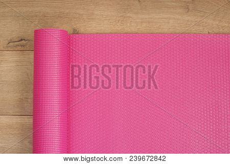 Pink Yoga Mat On A Wooden Background. Fitness Concept, Active Lifestyle, Body Care Concept. Wood Bac