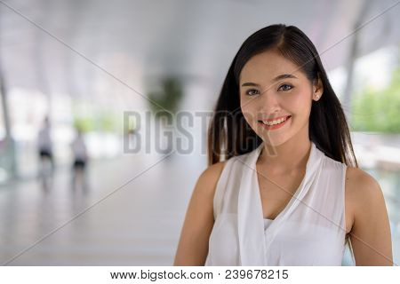 Portrait Of Young Beautiful Asian Businesswoman Hanging Out At The Footbridge In Bangkok, Thailand
