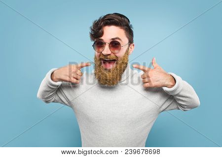 Excited Man In Sunglasses And Sweater Pointing At Beard In Golden Dust Looking Excitedly At Camera.