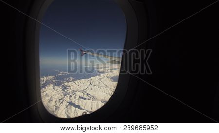 Mountain Range With Snow From The Airplane Window. Airplane Wing. Aerial View On Snowy Mountains Thr