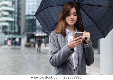 Attractive Female Manager Using Mobile Phone In Modern Area, Young Girl Browsing Phone Smiling Under