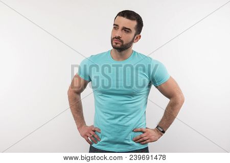 Handsome Man. Strong Nice Man Standing Against White Background While Looking In Front Of Him