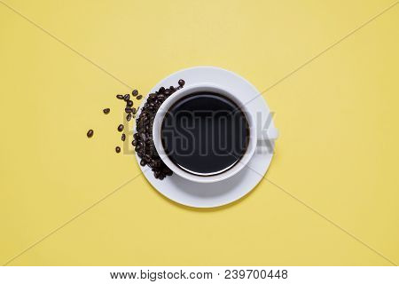 Coffee Cup On Saucer With Spilled Beans On A Bright Yellow Background