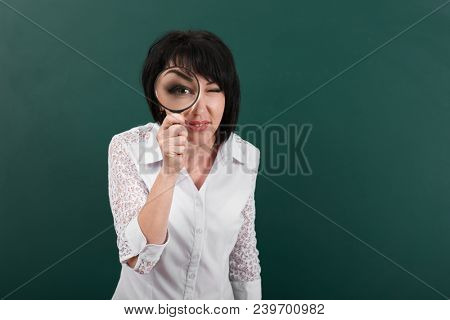 a woman looks forward through a magnifying glass, a blackboard as a background, big eye is visible inside the magnifier, a concept of education and business