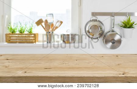 Wooden Table Top On Blurred Kitchen Interior With Copy Space