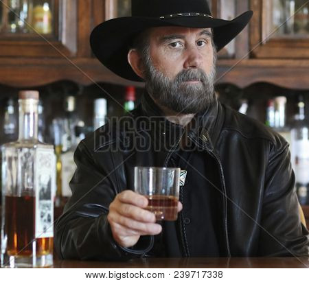 A Bearded Cowboy In Black Sitting Alone In A Saloon Drinking Whiskey