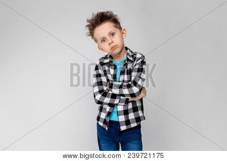 A Handsome Boy In A Plaid Shirt, Blue Shirt And Jeans Stands On A Gray Background. The Boy Folded Hi