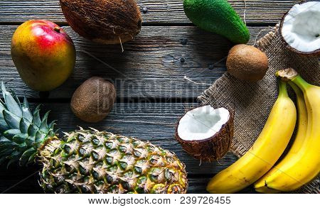 Pineapple With Banana, Mango, Avocado And Coconut On Wooden Background. Fruit, Food, Nature A