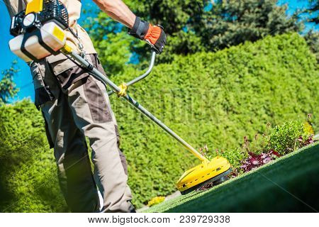 Gas String Trimmer Work. Caucasian Gardener With Power Tool In The Garden.