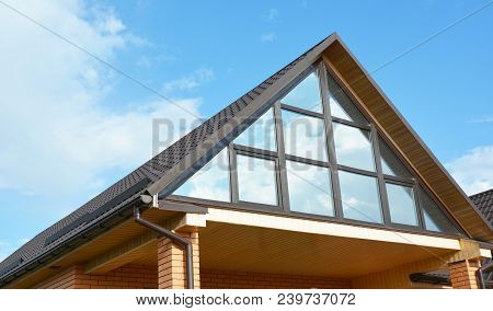 Modern House Attic Construction With Roof Guttering And Panoramic Mansard, Attic Skylight Window.  A