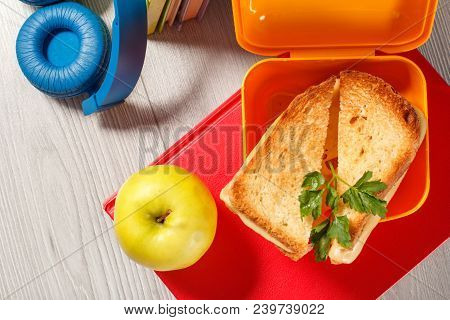 Yellow Sandwich Box With Toasted Slices Of Bread, Cheese And Green Parsley, Green Apple, Headphones